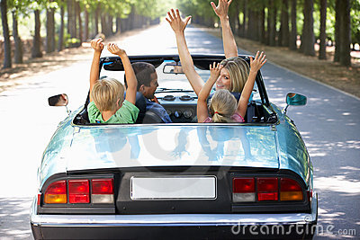 Family driving along in a sports car