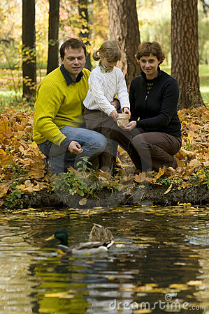 Family and ducks in autumn park