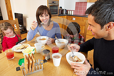 Family Eating Breakfast Whilst Children Play