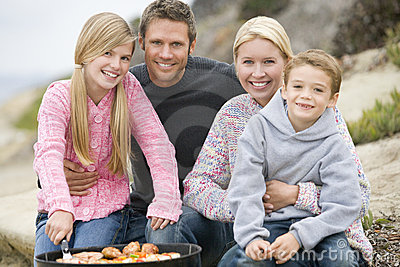 Family Enjoying A Beach Barbeque