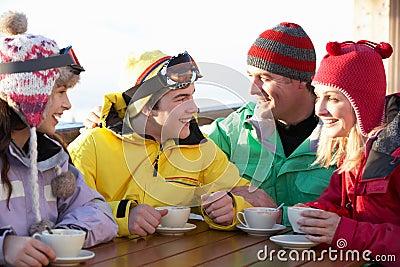 Family Enjoying Hot Drink In Cafe At Ski Resort
