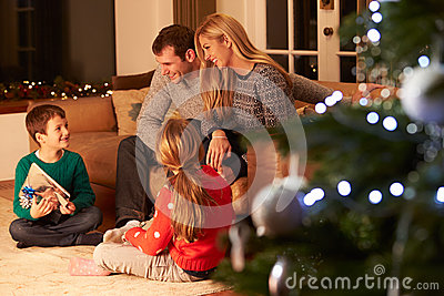 Family Exchanging Gifts By Christmas Tree Stock Photo