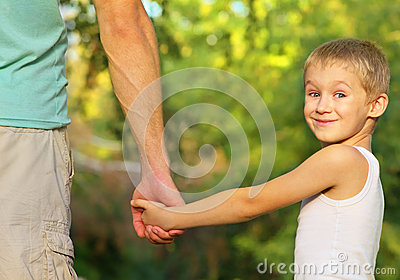 Family Father Man and Son Boy Child holding hand in hand Outdoor