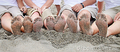 Family feet on beach in line