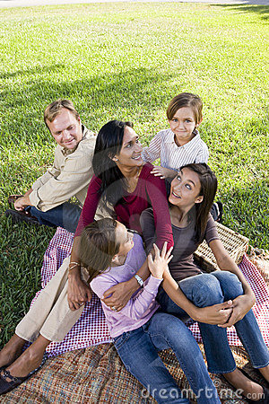 Family of five having picnic in park