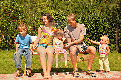 Family of five sit on bench