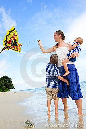 Family flying kite on tropical beach