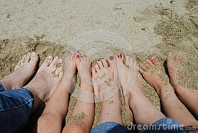Family feet on the beach