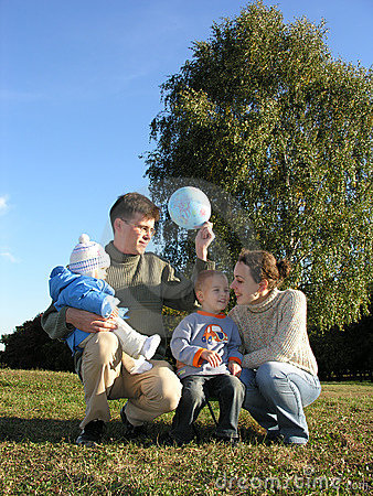 Family of four on grass blue sky autumn 2