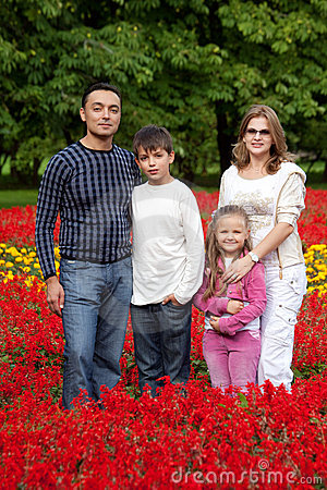 Family of four persons in flowering park