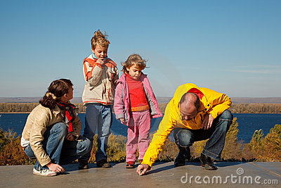 Family from four persons walks in solar autumn day