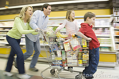 Family Of Four Running With Full Shopping Trolley