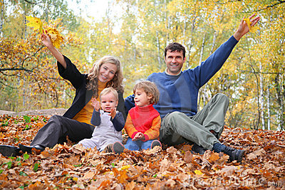 Family of four sits in autumn park.