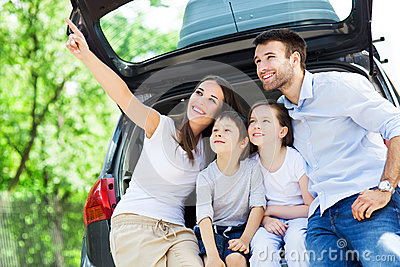Family of four sitting in car trunk