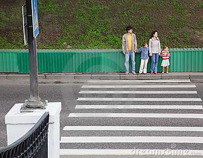 Family of four standing near pedestrian crossing
