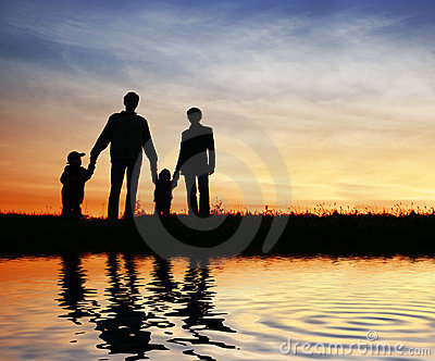 Family of four on sunset sky