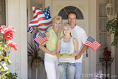 Family at front door on fourth of July with flags