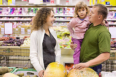 Family with girl buy pumpkin in supermarket