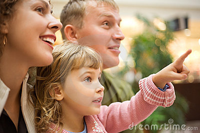 Family with girl with hand pointing finger forward