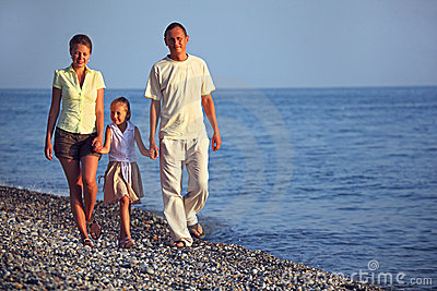 Family with girl walks along sunset sea beach