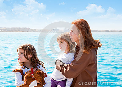 Family girls with dog on the sea