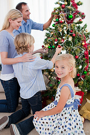 Family hanging decorations on a Christmas tree