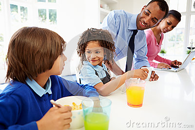 Family Having Breakfast In Kitchen Before School And Work ...