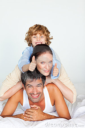 Family having fun in bed with thumbs up