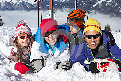 Family Having Fun On Ski Holiday In Mountains