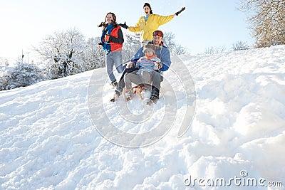 Family Having Fun Sledging Down Snowy Hill
