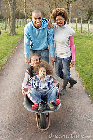 Family Having Ride In Wheelbarrow In Countryside
