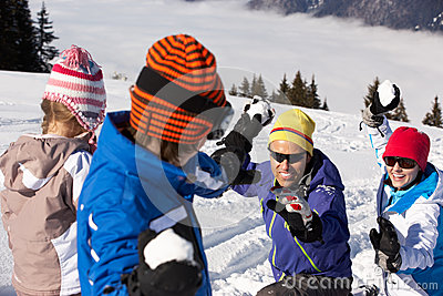 Family Having Snowball Fight On Ski Holiday