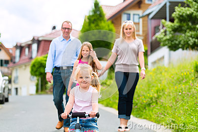 Family having walk in front of homes in village