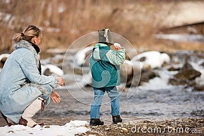 Family having winter walk at river
