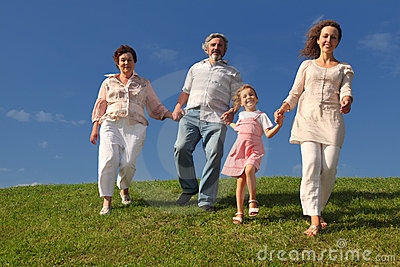 Family holding for hands and walking on lawn Stock Photo