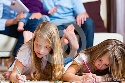 Family at home, the children coloring on floor Stock Photo