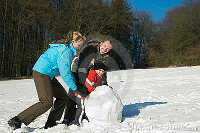 Family with kids making snowman
