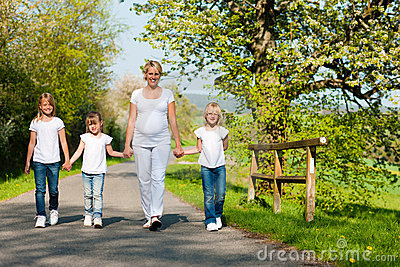 Family - kids and mother walking down a path