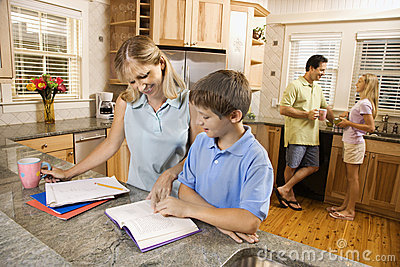 Family in kitchen doing homework.