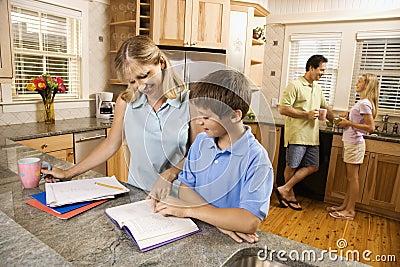 Family in kitchen doing homework.