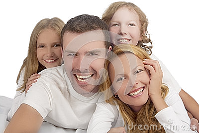 Family laughing together while laying on bed covered with white