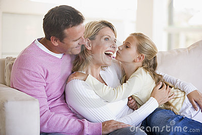 Family in living room with young girl kissing woma
