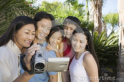 Family Looking at Video Camera Screen in back yard front view