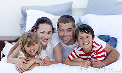 Family lying in bed together