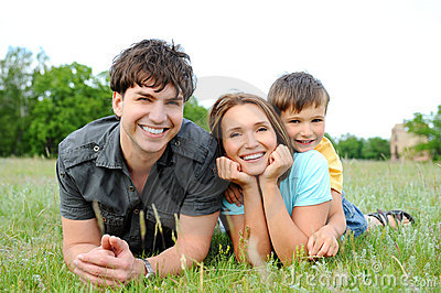 Family lying on the  green grass