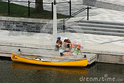 Family and Moored Canoe Editorial Image