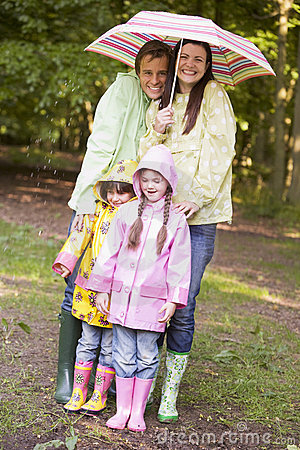 Free Family Outdoors In Rain With Umbrella Smiling Royalty Free Stock Photos - 5936418