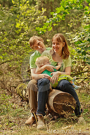 Family outdoors sitting on log smiling