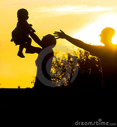 Family parents and child silhouette by sunset