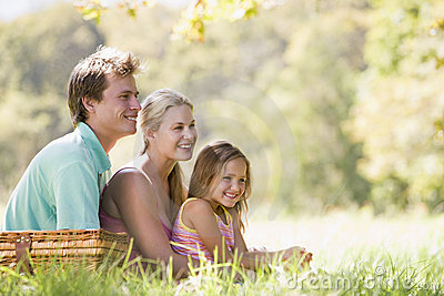 Family at park having a picnic and smiling